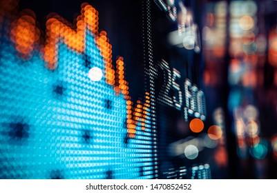 Anzeige von Börsenkursen mit Stadtlampen reflektiert auf Glas