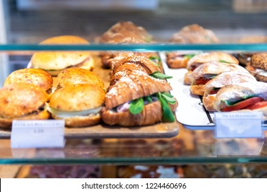 Display of store, shop selling Italian panini sandwiches with deli bologna meat, ricotta cheese, tomatoes, green spinach, buns, croissants on tray, platter
