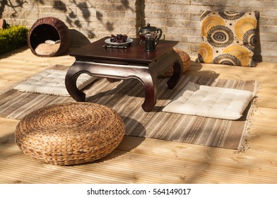 Display of table, table, cat bed, rug, Moroccan cushion, chinese umbrella and wicker stool on the decking area of a Zen style garden in Edinburgh, Scotland, UK, with a wall on the background.