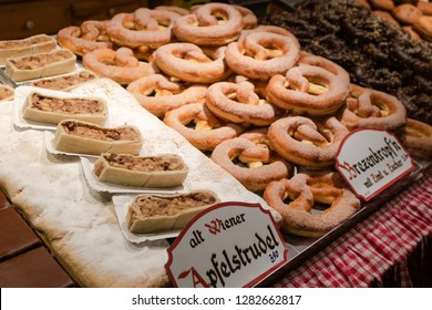 Display of traditional doughnuts on sale at Christmas market stall in Austria (translation: Old Viennese apple strudel; brezen doughnut with cinnamon and sugar)