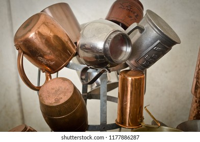 Display tree of pewter silver and copper cups tankards with a rustic white canvas background.