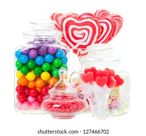 A display of various candies in glass containers.  Shot on white background.