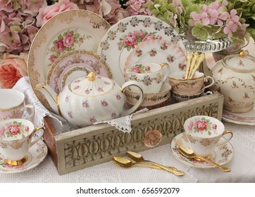 Display of vintage plates, teacups and teapots in an vintage distressed wooden drawer