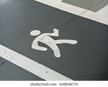 Displayed sidewalk in gray with white bars on the side and painted running males in a parking garage for the orientation of the people, so that they find their way and are safe from the passing cars