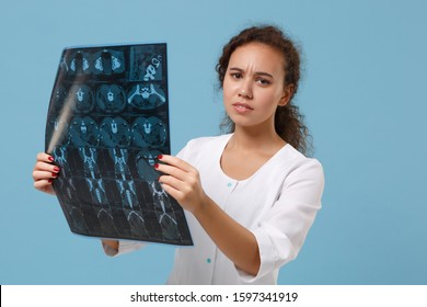 Displeased african american doctor woman in medical gown hold x-ray the brain by radiographic image ct scan mri isolated on blue background. Healthcare personnel medicine concept. Mock up copy space