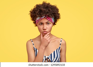 Displeased angry dark skinned young woman holds chin, claims about something bad, has sullen expression, crisp hair, wears headband, models against yellow background. Negative emotions concept