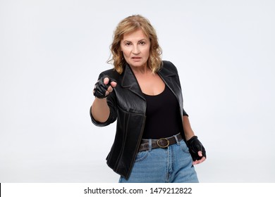 Displeased angry woman in leather jacket pointing finger at camera blaming you in problems.