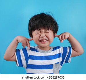 Displeased Asian Boy covering his Ears from the Noise.