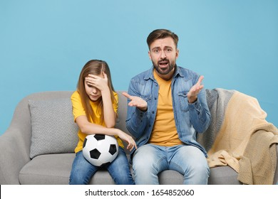 Displeased bearded man with child baby girl. Father little kid daughter isolated on pastel blue background. Love family parenthood childhood concept. Cheer up support favorite team with soccer ball