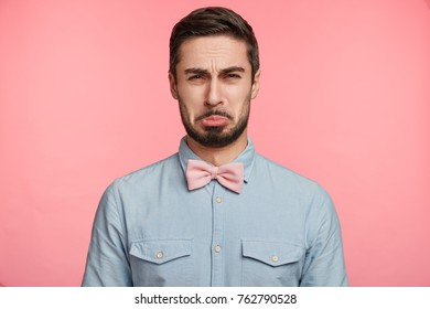 Displeased bearded young male finds out awful news about best friend, has spoiled party, looks miserable and dispirited, curves lips, expresses melancholy or discontet. Negative human emotions