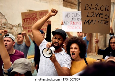 Displeased black couple shouting while marching with group of people on  anti-racism protest.