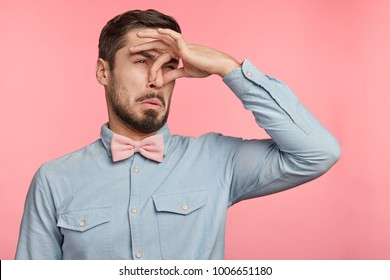 Displeased brunet male plugs nose as smells something stink and unpleasant, feels aversion, isolated over pink background. Young attractive man hates disgusting scent which comes from next room
