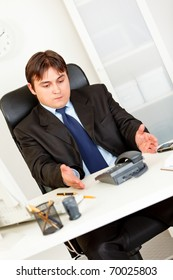 Displeased business man sitting at office desk and waiting important phone call