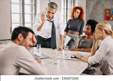 Displeased businessman arguing with colleagues on a meeting in the office and scolding one of them.
