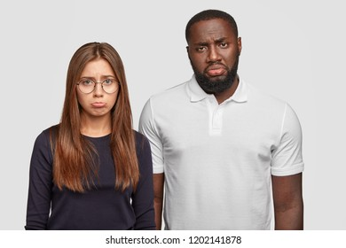 Displeased classmates have miserable facial expressions, purse lips with negative emotions, feel dejected, have problems with studying, cant find common language, isolated on white studio wall
