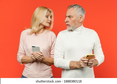 Displeased couple two friends elderly gray-haired man blonde woman wearing white pink clothes using mobile cell phone typing sms message isolated on bright orange color background studio portrait