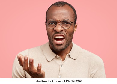 Displeased dark skinned guy frowns face in discontent, feels aversion, shows teeth, stands indoor against pink wall, dressed in beige t shirt. African American man under pressure. Anger and annoyance