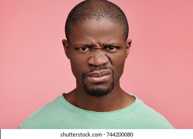 Displeased discontent African American male frowns face, dislikes something, looks with disgusting expression, isolated ovr pink background. Attractive unhappy young man isolated over pink background