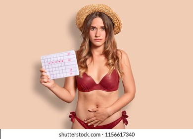Displeased European woman feels pain during menstruation, keeps hand on bottom of belly, holds period calendar, wears summer hat and swimsuit, isolated over studio background. Female has periods
