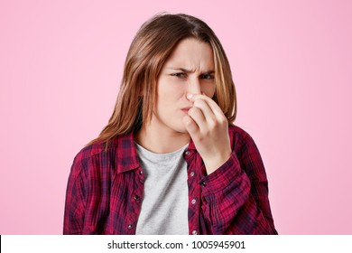 Displeased female model plugs nose as smells unpleasant scent, something disgusting and stinky, has unhappy and irritaed look, isolated over pink background. Lovely woman feels stink indoor.