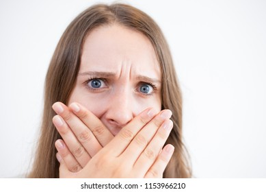 Displeased frowning young woman covering mouth with hands and looking at camera. Close-up of shocked girl being ashamed of her teeth. Bad breath concept