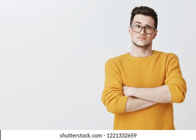 Displeased guy waiting for explanations. Confused doubtful and dissatisfied young handsome caucasian male in yellow sweater and glasses crossing hands on chest in hesitation and uncertainty
