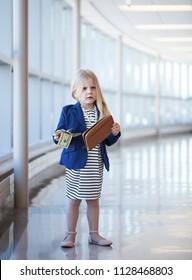 Displeased little girl holding dollars in shopping mall