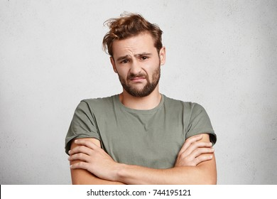 Displeased man with beard and mustache frowns face, expresses hesitation and concern, crosses hands, dressed casually. Unsatisfied male looks tired after long sleepless night and work on project