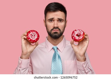 Displeased man with dark stubble, frowns face, holds two tasty ring donuts, feels unhappy as cant eat sweets, dressed in formal shirt with tie, isolated over pink background. Confused stressed male