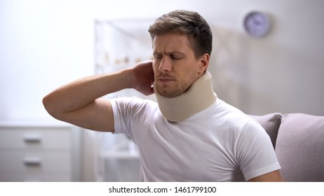 Displeased man in foam cervical collar suddenly feeling pain in neck, trauma
