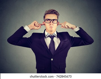 displeased man plugging ears with fingers doesn't want to listen isolated on gray wall background