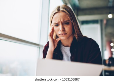 Displeased and sad young woman with blonde hair learning infromation from documents during hard work in office interior.Tired student spending time in university.Fatigued hipster girl