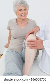 Displeased senior woman getting her knee examined at the medical office