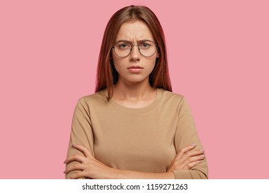 Displeased sullen female has discontent expression, keeps hands crossed, shows her dislike, frowns face, feels unhappy, has staight dark hair, poses against pink background. Negative emotions concept