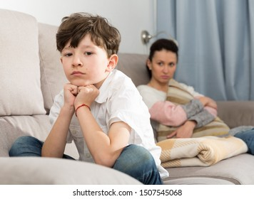 Displeased teen boy dont speaking after discord with mother at home