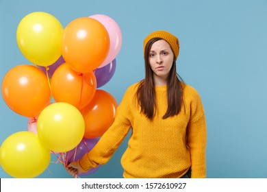 Displeased tired young woman girl in sweater hat posing isolated on blue background in studio. Birthday holiday party people emotion concept. Mock up copy space. Celebrating hold colorful air balloon