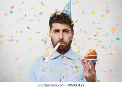Displeased unhappy bearded Caucasian man with cone hat on head and party horn in mouth looking at camera with bored dissatisfied expression as his birthday party sucks. People and lifestyle