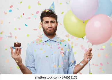 Displeased upset adult unshaven male worker in shirt screwing mouth, looking mournful and unhappy, doesn't want to get old, standing in office with cupcake and colorful balloons in his hands