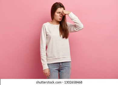 Displeased woman covers nose with hand, smells something awful, pinches nose, frowns in displeasure, sees pile of garbage, dressed in casual clothes, isolated over pink background. Bad odour.