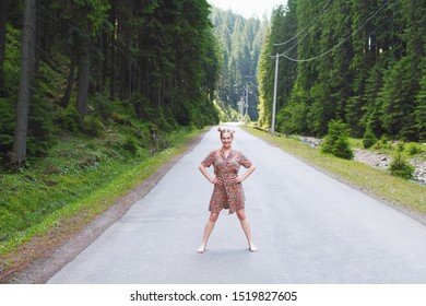 Displeased woman standing in a dress in the center of the road in the mountains. Hands on the belt.