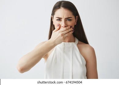 Displeased young brunette girl covering mouth with hand looking at camera over white backround.