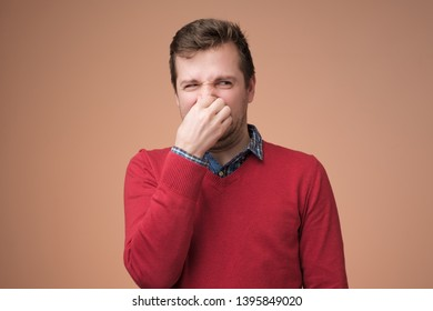 Displeased young man in red sweater plugs nose as smells something stink and unpleasant, feels aversion. Guy hates disgusting scent which comes from somewhere