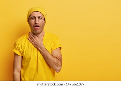 Displeased young man suffers from suffocate, has painful feelings in throat after loud shouting, touches neck, shows tongue, has asthmatic fit, needs doctors help. Health problem and sore throat
