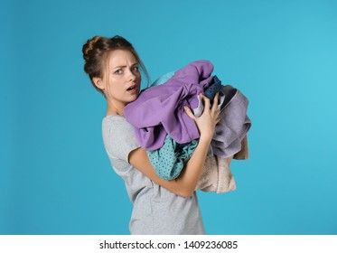 Displeased young woman holding pile of dirty laundry on color background
