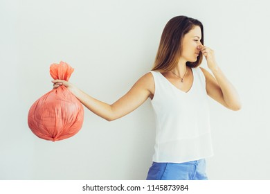 Displeased young woman with pinched face holding garbage bag and holding her nose. Unpleasant smell concept