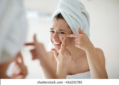 Displeased young woman squeezing pimples in front of mirror