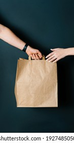 Disposable bag of kraft paper. Food delivery, hand-to-hand package transfer. Minimalist design, stylish wall color. Kraft design.