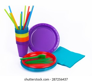 Disposable bright plastic kitchenware and napkins isolated on white backgound