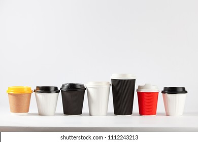 Disposable coffe cups different colors and sizes in a row on white background with copy space