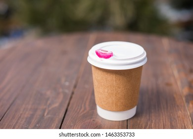 Disposable coffee cups with lipstick mark. On wooden table.